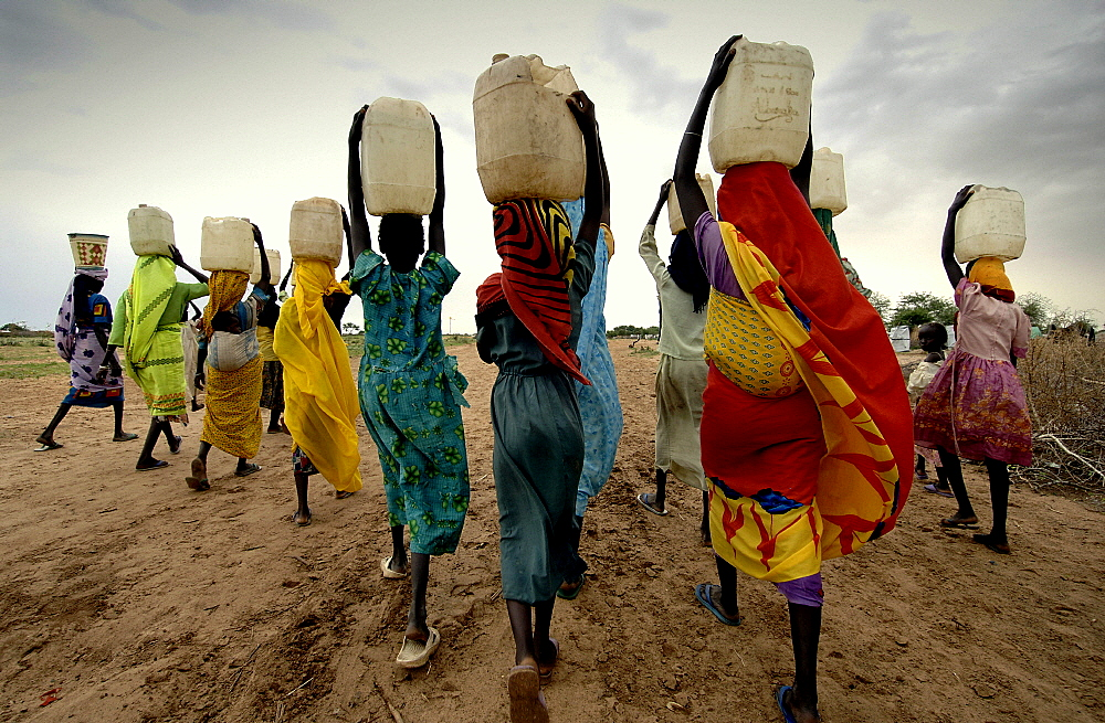 Women carrying water collected from taps installed by international aid agencies in a camp for internally displaced persons (IDPs). They fled their homes after being attacked by Janjaweed militias.