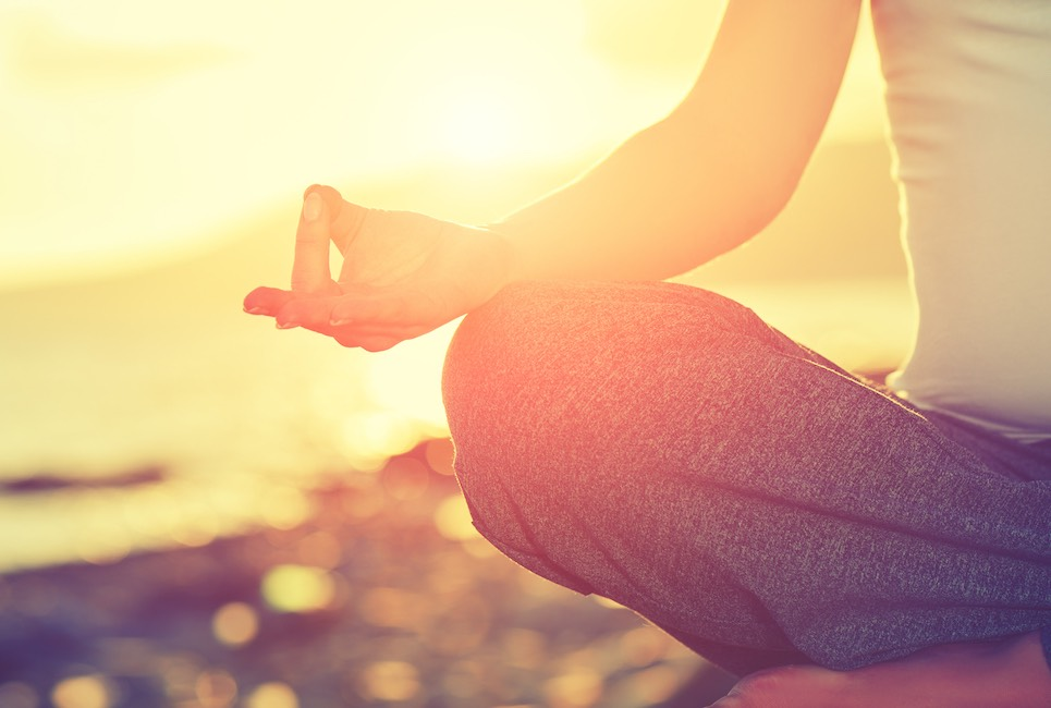 Yoga concept. hand woman practicing lotus pose on the beach at sunset